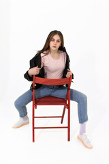 A girl in jeans sits on a chair and straightens her jacket.