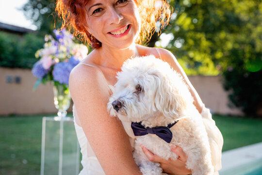Cheerful adult bride hugging dog in garden