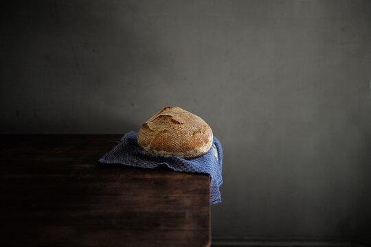 Fresh baked French organic spelt sourdough bread in the kitchen  or bakery on a blue linnen towel