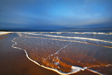 A view from the snow-covered sandy Baltic sea shore at sunset. Riga bay, Latvia. Dramatic blue sky. Fickle weather, waves and water splashes. Winter tourism, global warming theme