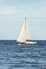 Small yacht sailing near the lighthouse on a clear day. Riga bay, Baltic sea, Latvia. Cruise, sport, recreation, leisure activity concepts