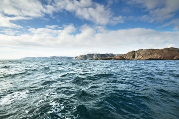 A view of the North sea from a sailing boat. Clear blue sky reflecting in the water. Fjords in the background. Hidra island, Rogaland region, Norway. Sport, recreation, environmental conservation