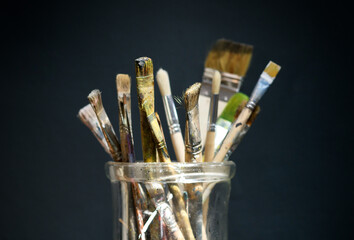 Collection of used paintbrushes in a jar