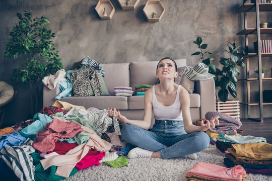 Full body photo of annoyed irritated girl house wife order wardrobe discover many dirty dressing clothes scream look sit floor carpet legs crossed folded in house indoors
