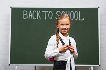 selective focus of adorable schoolgirl with backpack smiling at camera near chalkboard with back to...