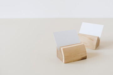 Blank paper cards with mockup copy space in card holders on beige background. Minimal business...