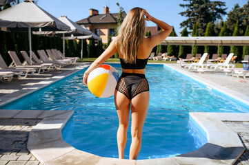 Sexy woman with ball at the poolside, back view
