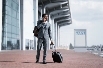 Serious Entrepreneur Talking On Cellphone Standing Near Airport, Full-Length