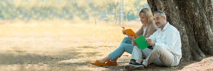 senior woman sitting on a fallen autumn leaves reading a book with husband or friend in a park, relax and vacation concept