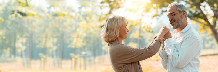 senior woman and man hug together and kiss on wife's hand on a fallen autumn leaves in a park, love old couple concept