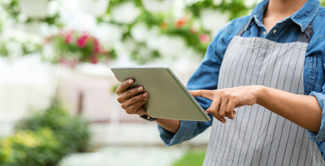 Easy work with modern technology in greenhouses. African american woman working with digital tablet