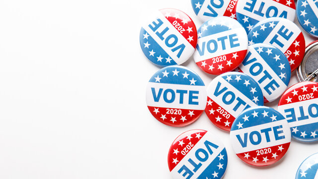 Pile of patriotic voting buttons on white background