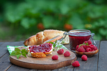 Breakfast with fresh roll and raspberry jam. Homemade raspberry marmalade in a jar with fresh fruit on rustic, wooden table