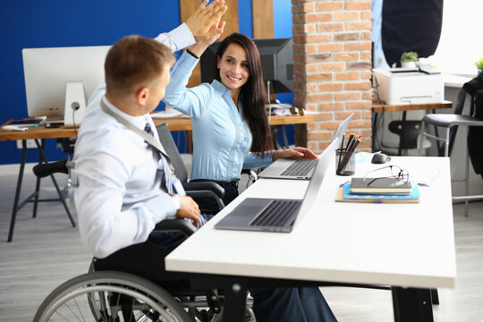 Disabled businessman sits in wheelchair at work table in office and greets businesswoman. Effective teamwork of volunteers concept
