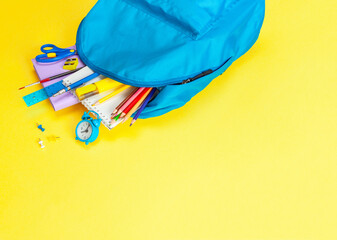 School bag. Backpack with supplies for school on yellow background. Copy space for text