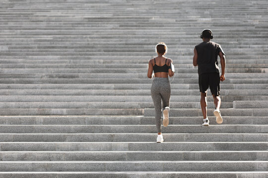 Outdoor sport. Black couple running on stairs in city park, rear view