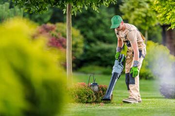 Gardener with Cordless Leaf Blower Cleaning Backyard Garden