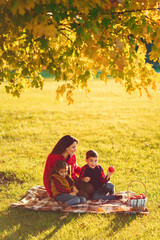 Cute family in a autumn park. Happy mother with little kids. Family sitting on yellow leaves. Golden autumn.