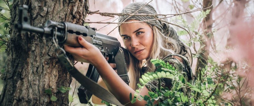 Beautiful and attractive woman soldier shooting with rifle machine gun in the forest. Female  army nature outdoor military combat training. Femme fatale