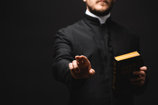 selective focus of priest holding holy bible while gesturing isolated on black