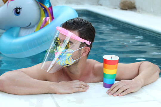 Attractive man wearing protective face mask in swimming pool