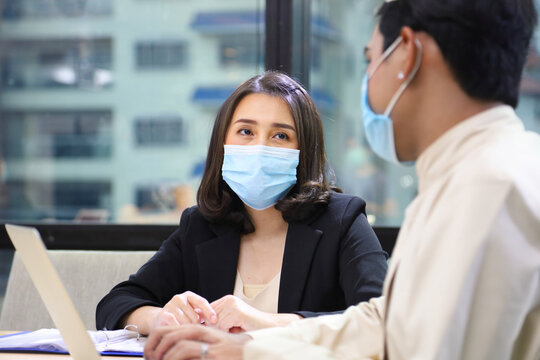 Business women in formal wear with protective facial mask discussing with colleague in business office following new normal and social distancing policy during covid-19 or coranavirus pandemic