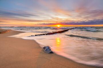 Zachód słońca nad morzem na plaży - fototapety na wymiar