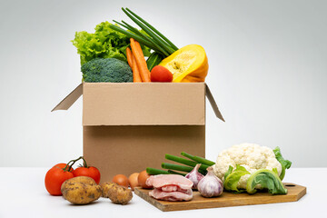 fresh organic local farm food - group of vegetables eggs and meat in cardboard box