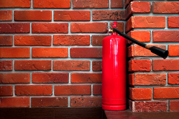 Fire safety background with fire extinguisher on the red bricks wall
