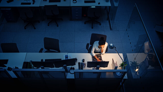 Working Late at Night in the Office: Businesswoman Using Desktop Computer, Analyzing, Using Documents, Solving Problems, Finishing Project. High Angle Shot