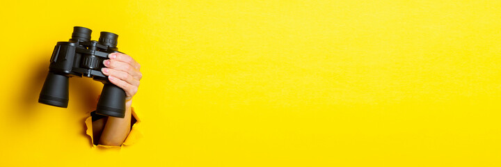 Female hand holds black binoculars on a yellow background. Looking through binoculars, travel, find and search concept. Banner. - fototapety na wymiar