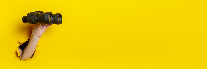 Female hand holds black binoculars on yellow background, travel, find and search concept. Banner. - fototapety na wymiar