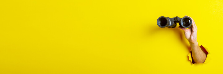 Fototapeta Female hand holds black binoculars on yellow background, travel, find and search concept. Banner obraz