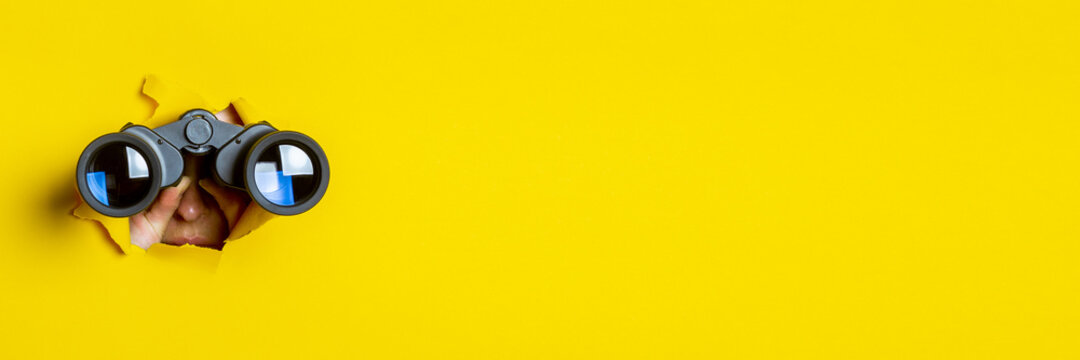Female hand holds black binoculars on a yellow background. Journey, find and search concept. Banner.