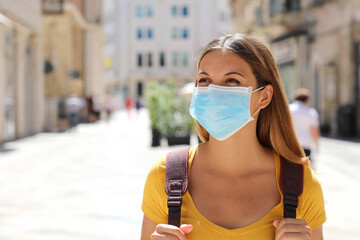 Young beautiful tourist woman wearing face mask while visiting European city