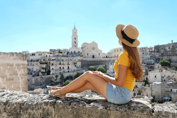 Beautiful young woman with hat sitting on wall looking at stunning panoramic view of Matera, Italy