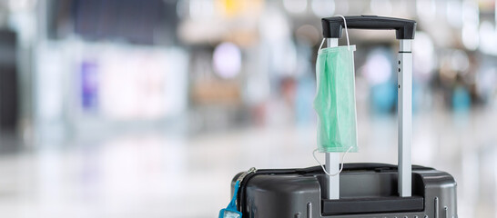 Luggage bag with surgical face mask and alcohol gel hand sanitizer in international airport...