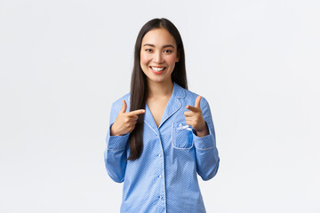 Cheerful cute asian girl smiling happy, standing in blue pajamas inviting girlfriends to sleepover...