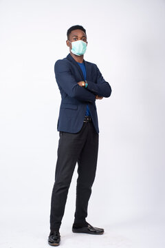young black business man wearing a suit and face mask standing confidently with arms crossed