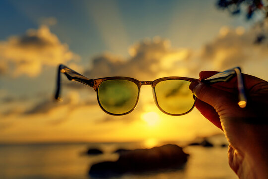 View of the sunset on the tropical sea through sunglasses in hand, abstract conceptual background of vacation and travel