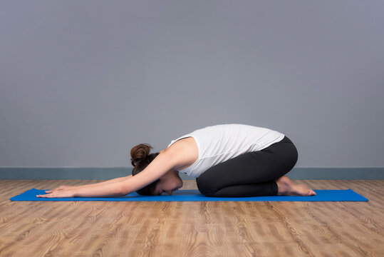 Asian woman practicing yoga pose at yoga healthy sport gym, yoga and meditation have good benefits for health.