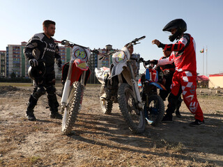 Members of a motocross team chat with each other after a training in Kabul