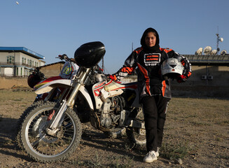 Negin Afshar, 16, one of motocross racers, poses for a picture after a training in Kabul