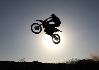 A member of motocross team performs a jump during a training in Kabul