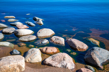 Stones in clear blue lake water. Lake Ladoga, Russia.