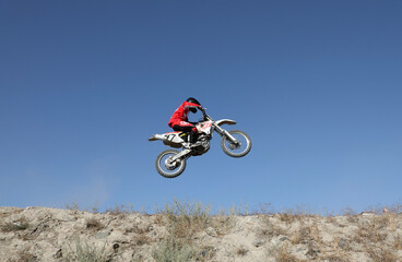 A member of a motocross team performs a jump during a training in Kabul
