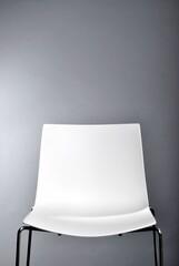 leerer weißer Stuhl vor grauem Hintergrund