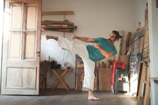 Man doing a martial arts pose in an artist studio
