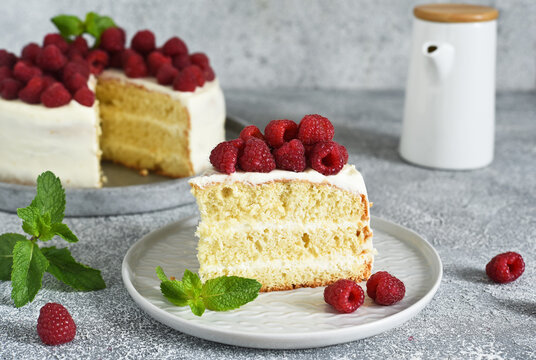 Slice of cake. Birthday cake with cream cheese and raspberries and mint on a concrete kitchen background.