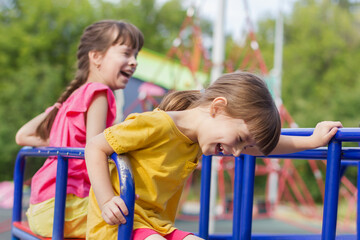 Poster de jardin Doux monstres two little girls laughting on a swing in the park